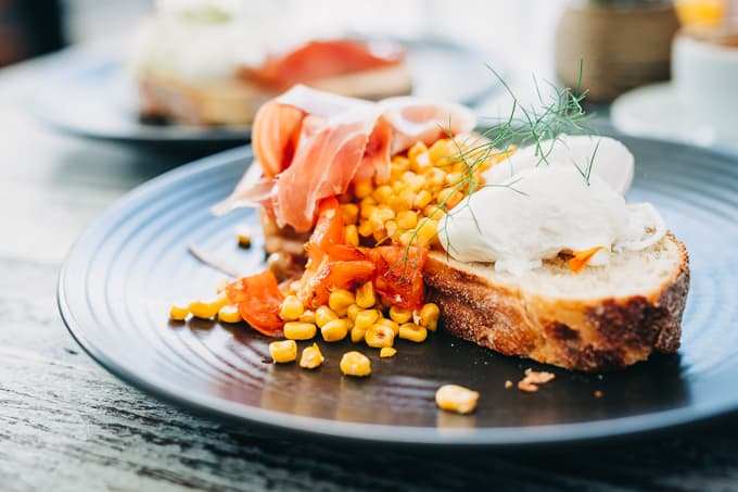 Overflowing kernels of corn with prosciutto, and perfectly poached eggs at Bellbird Dining and Bar